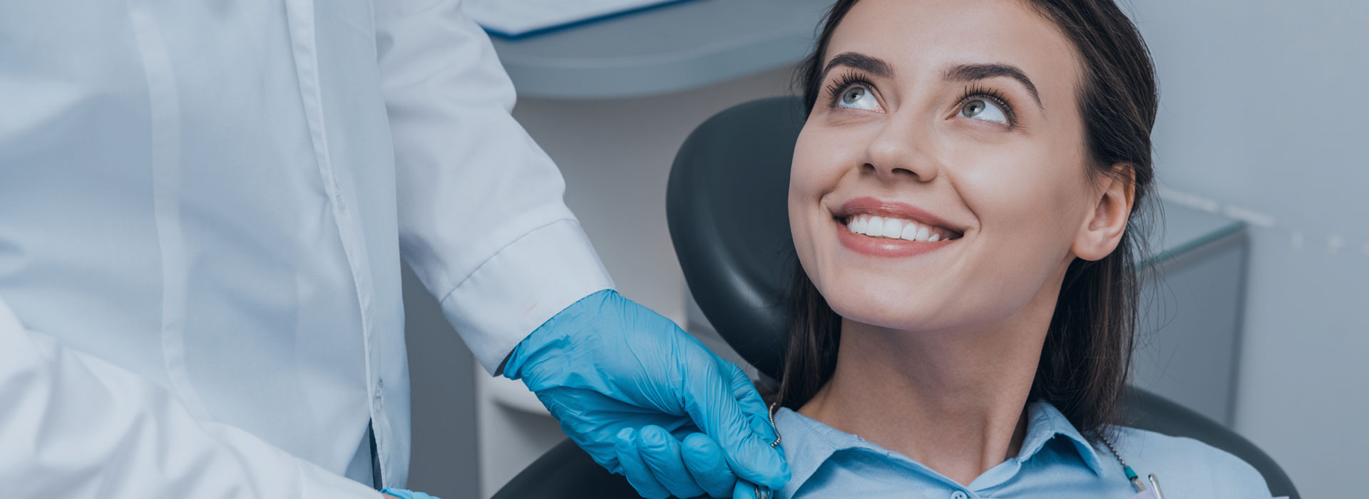 A woman is smiling after dental inlay